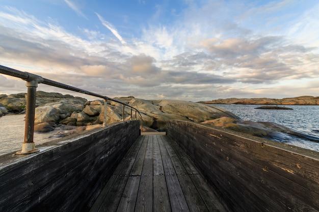 雲と空の上の木製の橋
