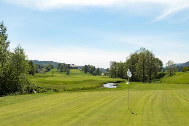 Поле для гольфа. отверстие с белым флагом в солнечный день