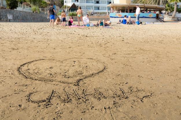 Я люблю канарские острова. рисунки в песке на пляже пуэрто-рико в гран-канария, испания.