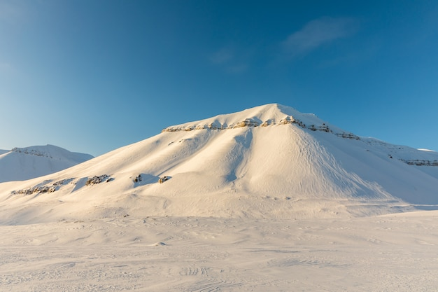 雪で美しい北極の冬の風景は、ノルウェーのスバールバル諸島の山々をカバー