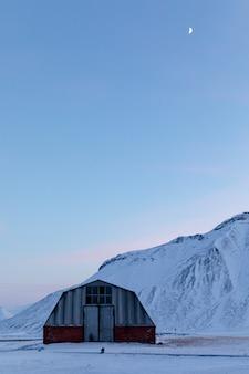 ピラミデンの古い建物、雪に覆われた山の後ろ、ノルウェー、スバールバル諸島ロングイェールビーンのイスフィヨルデン。