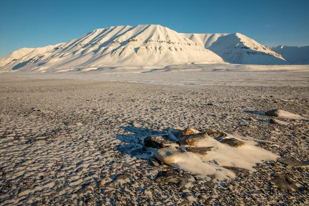 雪の北極の冬の風景は、ノルウェーのスバールバル諸島カプ・エクホルムの山々に覆われています