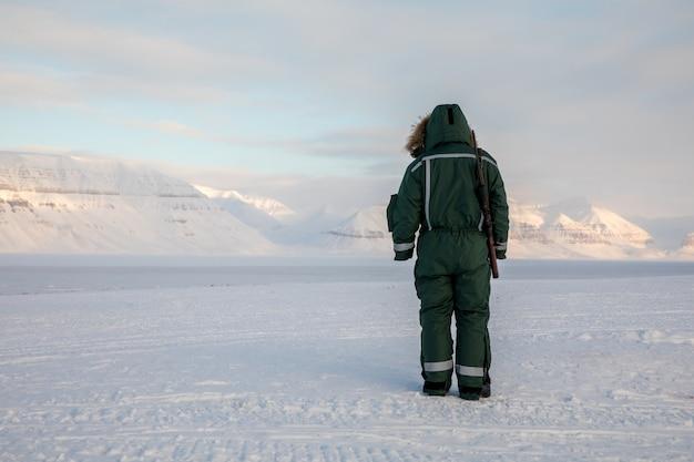ライフルを持つ男は、スバールバル諸島の北極の風景の地平線に見えます