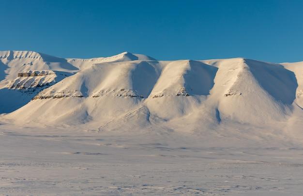 Арктический зимний пейзаж со снегом покрыл горы на шпицбергене, норвегия
