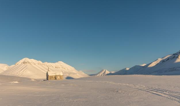雪で北極の冬の風景の中の小さな小屋は、ノルウェーのスバールバル諸島の山をカバー