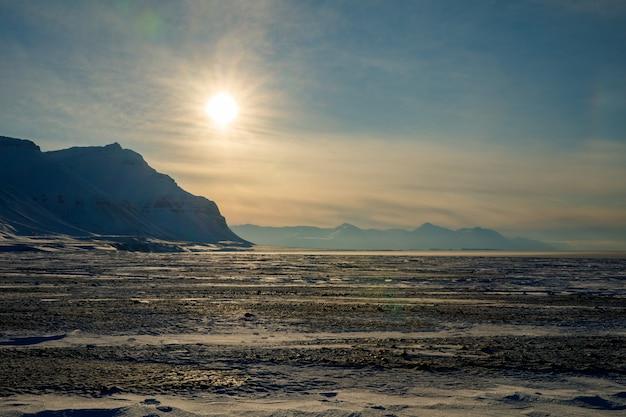 ビルフィヨルデン、スバールバル諸島の山の上の冬の太陽