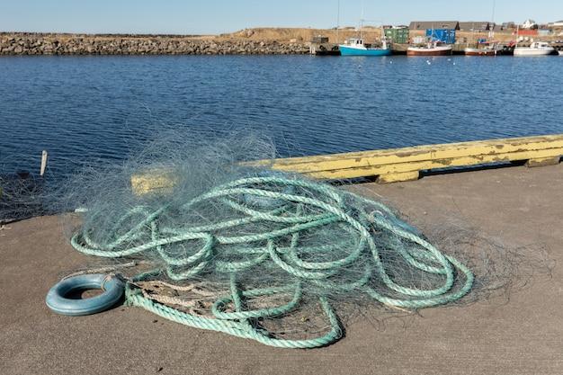 Зеленая рыболовная сеть в гавани с синим морем и рыбацкие лодки не сфокусированы