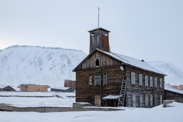 スバールバル諸島の古い放棄された建物。バックグラウンドで雪の山。