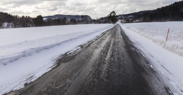 濡れて滑りやすい、冬のノルウェーの小さな道