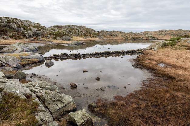 ノルウェーのハウゲスンにあるロヴァー諸島の小道にある池。水を通る道を作る石。