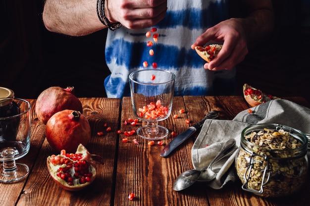 Человек кладет семена граната в стакан.