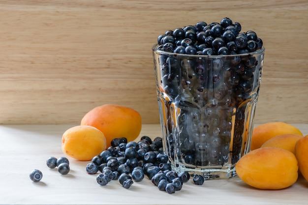Черника в стакане с рассеянными ягодами и несколькими абрикосами