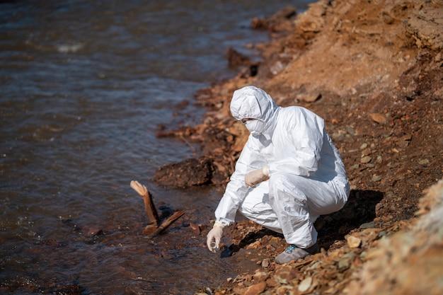 科学者または生物学者が水分析に協力する防護服を着ています。