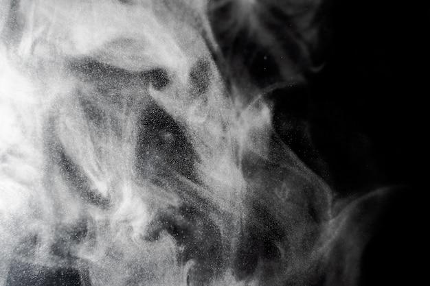 黒い背景に白い煙。煙のテクスチャ。オーバーレイの暗い背景に白い煙のクラブ
