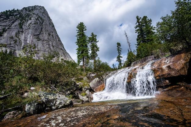 青空の下で山の森の高山の滝。