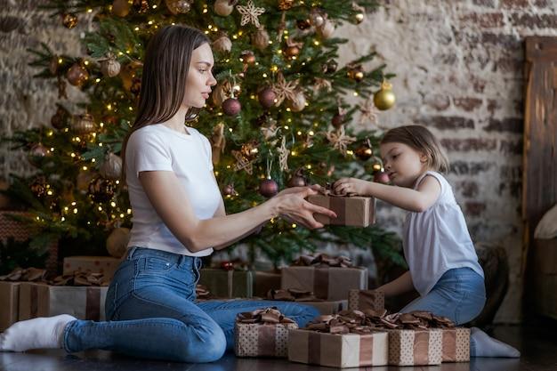 Счастливая семья, мать и дочка на рождественское утро у елки с подарками