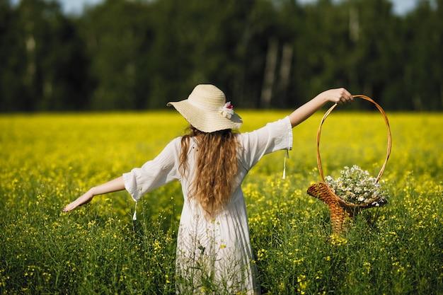 明るいドレスと麦わら帽子を着た女性が黄色い花畑を歩き、花のバスケットを手に持っています