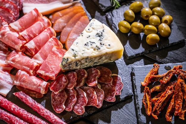 ブランチ。さまざまなチーズ、焼き肉、ソーセージ、オリーブ、ナッツ、フルーツの前菜テーブル。お祝いの家族やパーティーのおやつコンセプト。