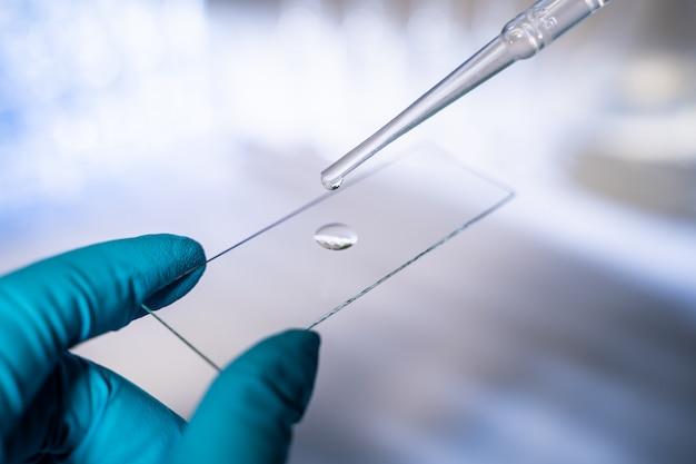 科学者は現代の研究室で働いています。ガラススライドに一滴の液体を塗ります