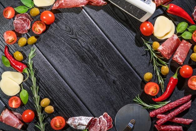 ピザ料理の食材。生地、野菜、スパイス。コピースペースのトップビュー