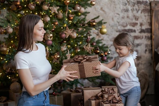 幸せな家族の母親と赤ちゃんの小さな娘がクリスマス休暇のために冬に遊んで