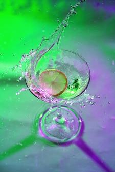 Коктейль маргарита с ломтиком лимона на бокале на цветном фоне