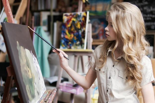 Художница рисует картину на холсте масляными красками в своей мастерской