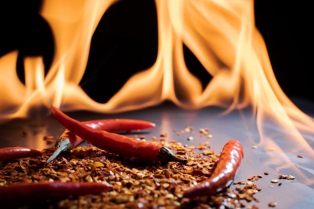 Красный острый перец чили у огня на черном фоне