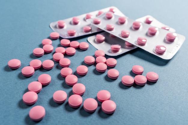 青色の背景にブリスターでピンクの丸薬