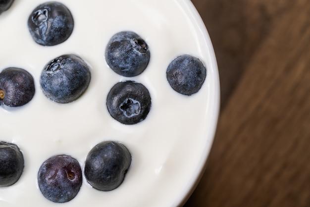 Йогурт с черникой реш, в миску на фоне старого дерева.
