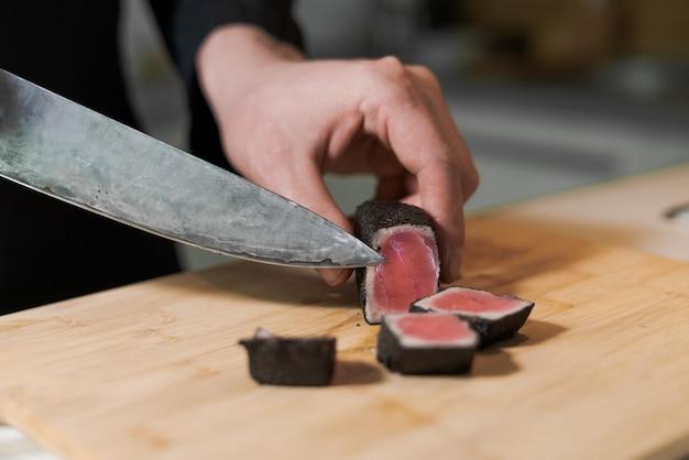 Кук нарезать ножом кусочки средне-редкого мяса тунца гриль на деревянной тарелке