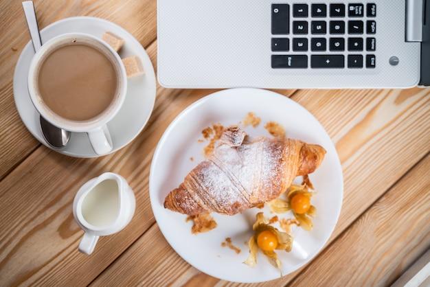 Легкий обед в офисе. кофе и круассан возле клавиатуры