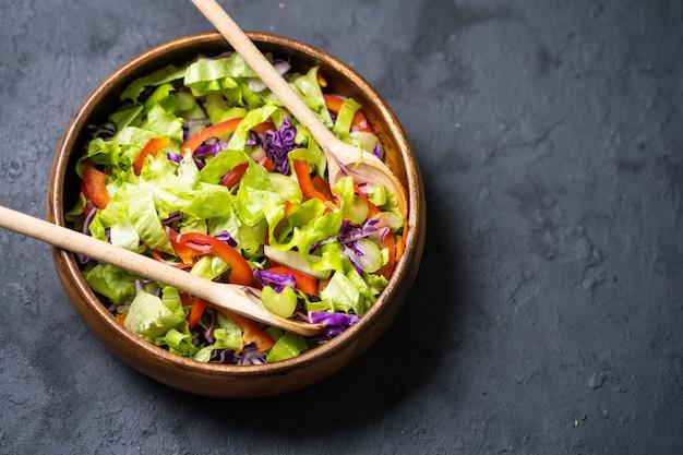 Здоровый овощной салат из свежих помидоров, огурцов, лука, шпината, салата и кунжута на тарелку.