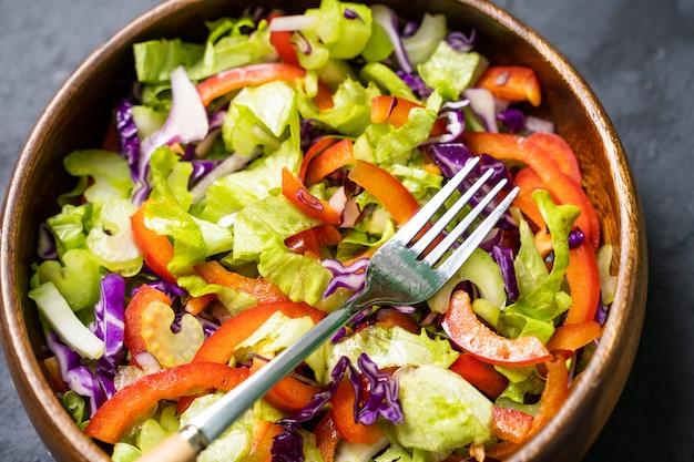 Салат салат, петрушка, красный лук в глиняной миске. вегетарианская здоровая пища.