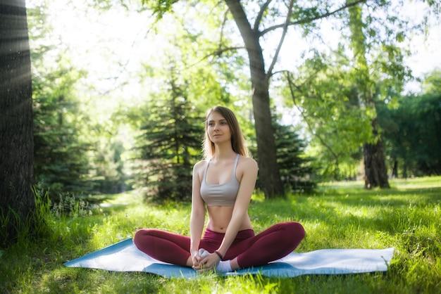 Девушка делает йогу в парке на летний день