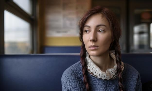 電車の窓から見ている若い悲しい女性。