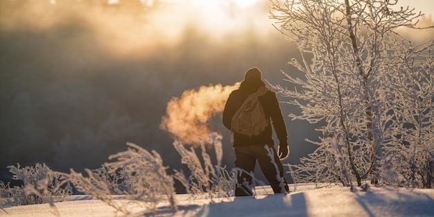 夜明けに雪に覆われた森の中を歩く残忍な観光客の男
