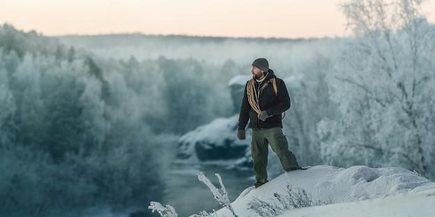 残忍な観光客の男が夜明けに川と岩を背景に雪に覆われた森の中を歩く