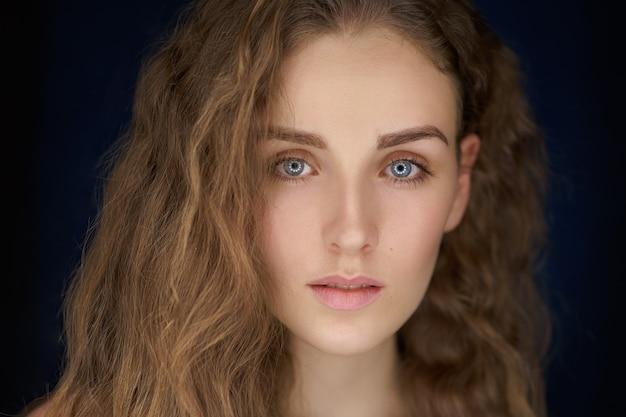 Макро портрет красивой женщины с длинными вьющимися светлыми волосами на черном фоне