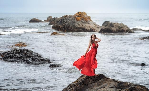 Красивая молодая девушка в длинном красном платье позирует на берегу океана на скалах