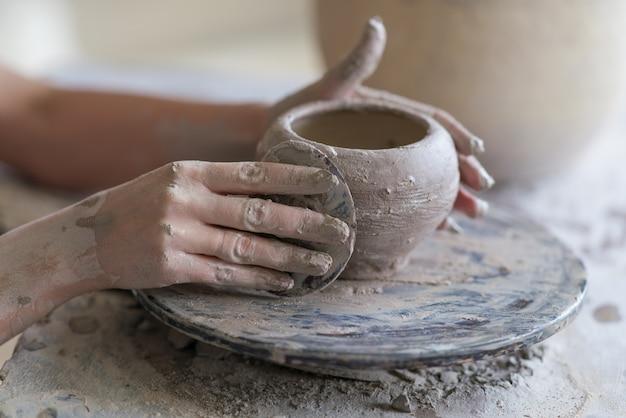 陶工は、ろくろの上に花瓶を彫る