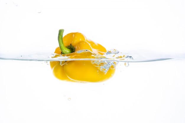 Перец в брызгах воды. сочный персик с всплеск