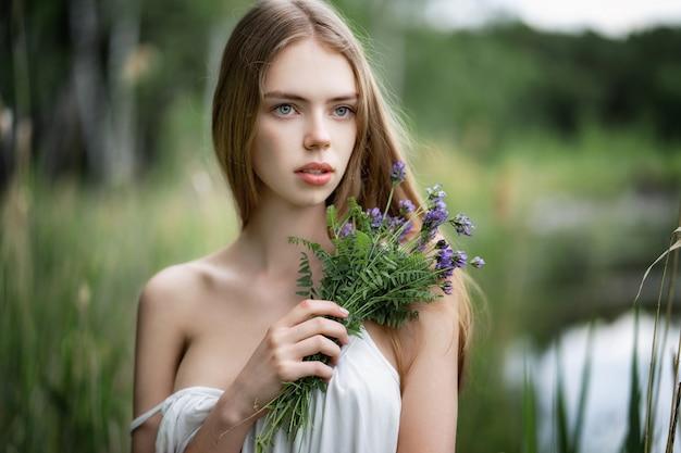 野生の花を持つ若い美しい女性の肖像画