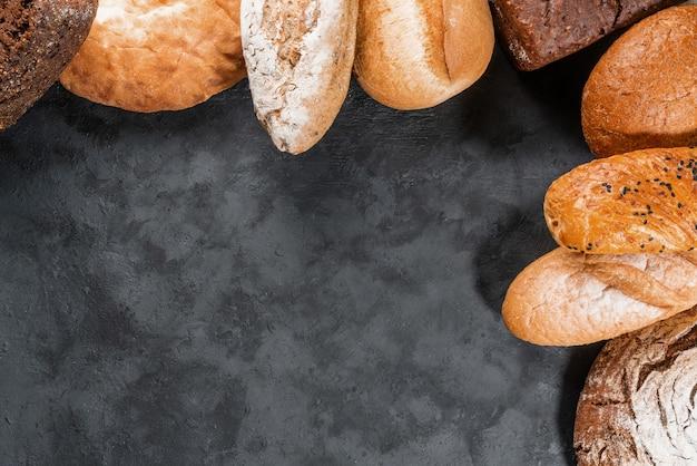 Свежая еда хлебопекарни, деревенские покрытые коркой ломтики хлеба на черном каменном фоне. вид сверху