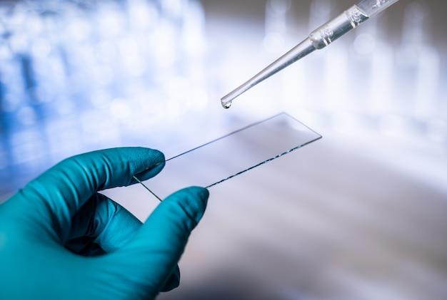 ソリューションで卵細胞を滴下実験室でピペットを扱う女性科学者