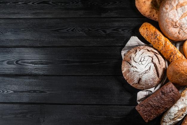 Различный покрытый коркой хлеб и плюшки на каменном столе. вид сверху
