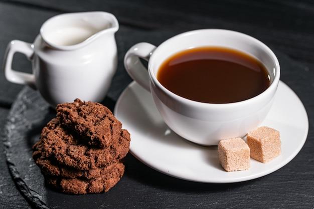 白いカップにミルク入りのコーヒー、ビスケットと砂糖を添えて