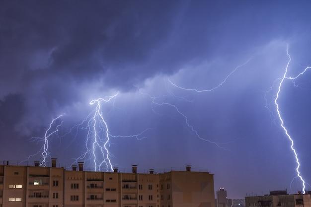 Молнии над городом в ночном небе попадают на крышу дома.