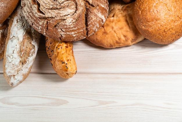 Мука в деревянной миске на темном деревянном столе с колосками пшеницы, яиц и молока, вид сверху с копией пространства