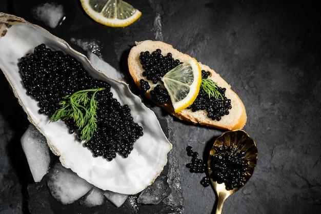 黒のチョウザメキャビアと黒のコンクリートテーブルの上の氷の上のレモンとカキを開きました。トップビュー、フラットレイアウト、コピースペース。